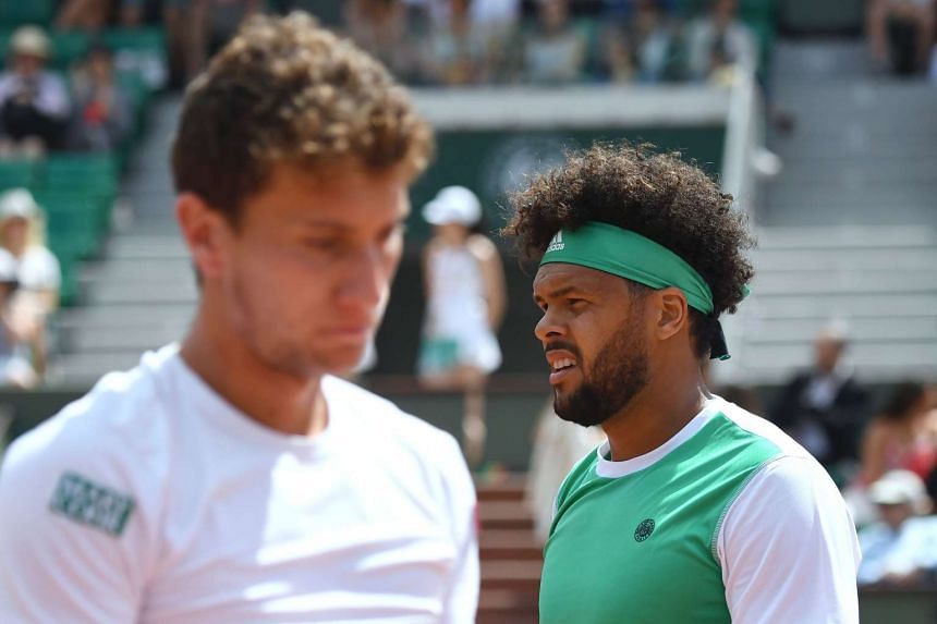 France's Jo-Wilfried Tsonga (right) walks past Argentina's Renzo Olivo during their match.