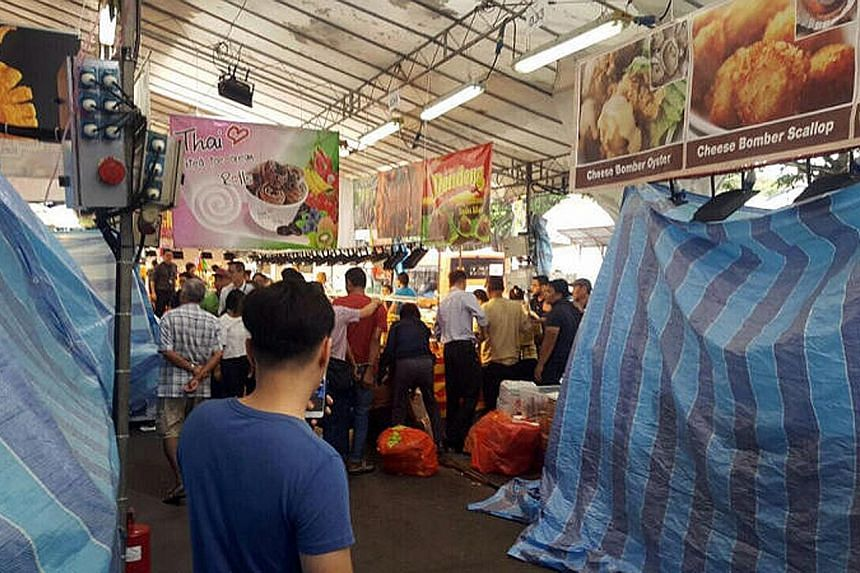Unregistered food handlers being arrested at the Geylang Serai Bazaar during a joint operation by MOM, NEA and the police yesterday.