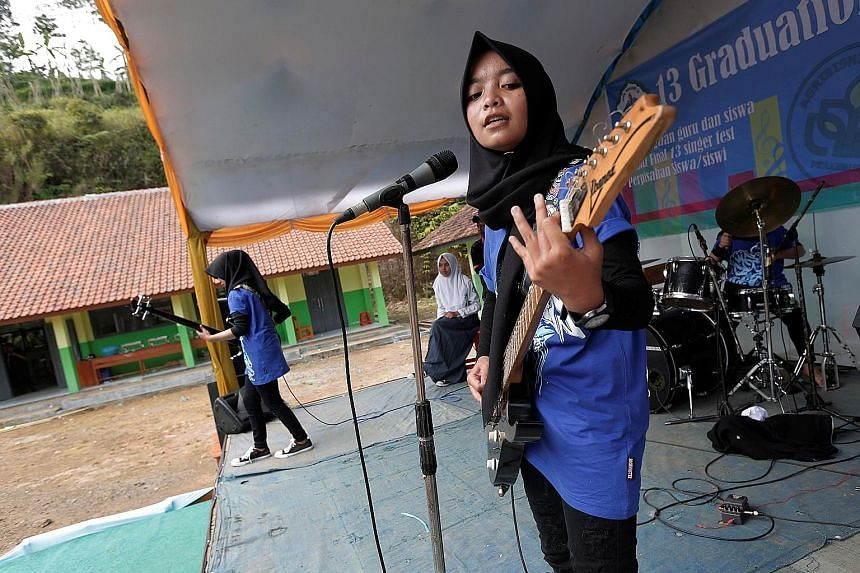 Heavy metal group Voice of Baceprot, led by Firdda Kurnia (right), performing during a school's farewell event in Garut, Indonesia.