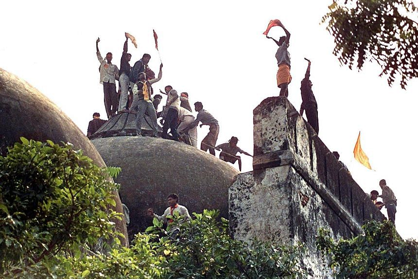 Above: Water Resources Minister Uma Bhartiwas among Mr Narendra Modi's party leaders who were charged yesterday. Right: People clamouring on top of Babri Mosque on Dec 6, 1992, five hours before the structure was demolished by hundreds supporting Hin