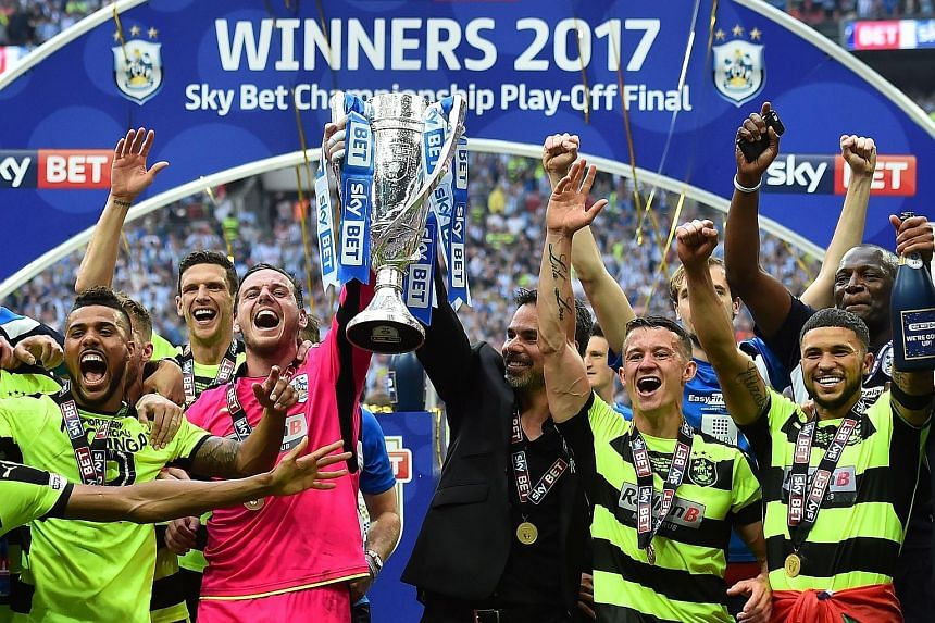 Huddersfield's players and manager David Wagner celebrating the club's historic promotion to the Premier League.