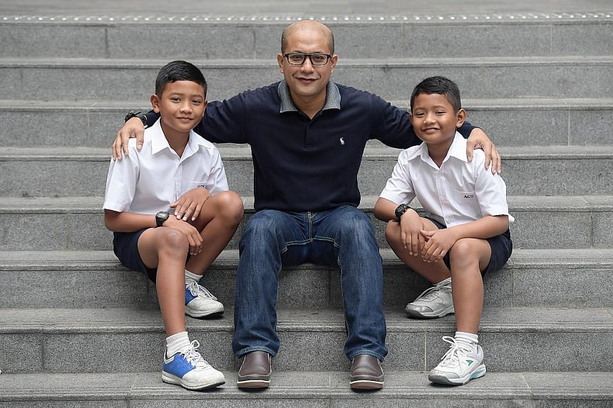 Brothers Muhammad Raihan (left), 12, and Muhammad Razin, 9, with their father, Mohd Airudin. They were among 335 student athletes who received SOF-Peter Lim scholarships yesterday. The $1,000 that the siblings each received will likely go towards the