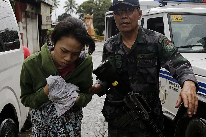 Philippine marines and commandos were clearing rebel positions house by house and street by street in Marawi yesterday. The military said its men have taken back most of the city. A villager getting help after she escaped an area controlled by milita