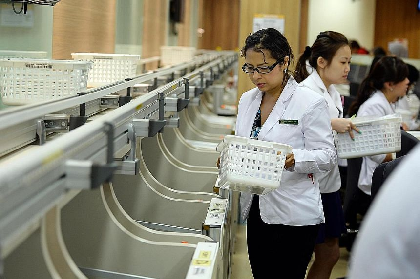 Pharmacy technicians picking up baskets containing medication for patients at the front counter delivered by a new automated system at the Singapore General Hospital's outpatient pharmacy. The system is among new IT innovations in the healthcare sect