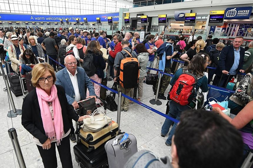 British Airways passengers in Heathrow Airport on Monday. The airline was due to resume a full flight schedule yesterday after a computer outage led to thousands of stranded passengers at the weekend.