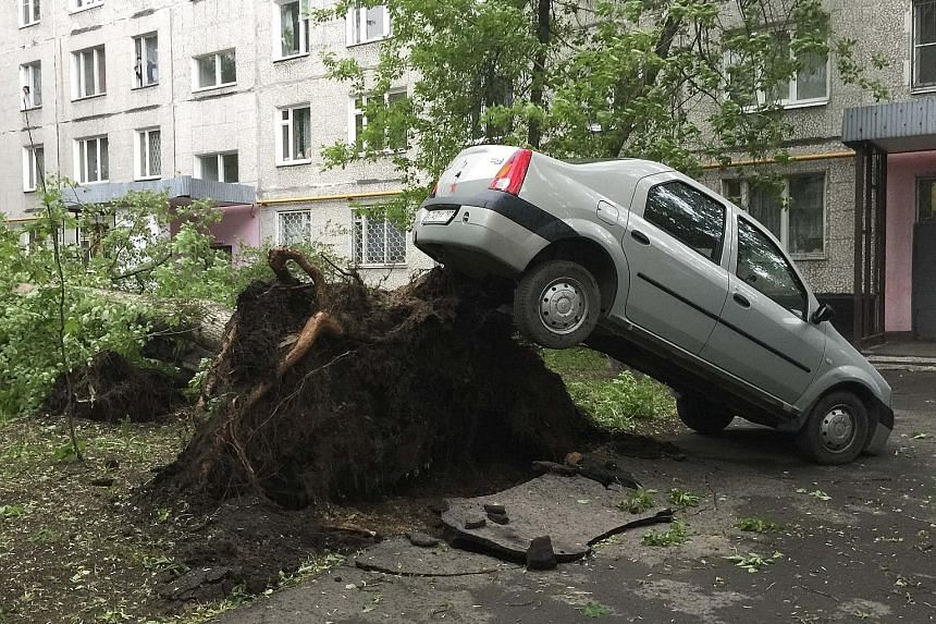 A car lifted by the roots of a tree, which toppled during a heavy storm, in Moscow, Russia, on Monday. Wind speed reportedly reached up to 103kmh.