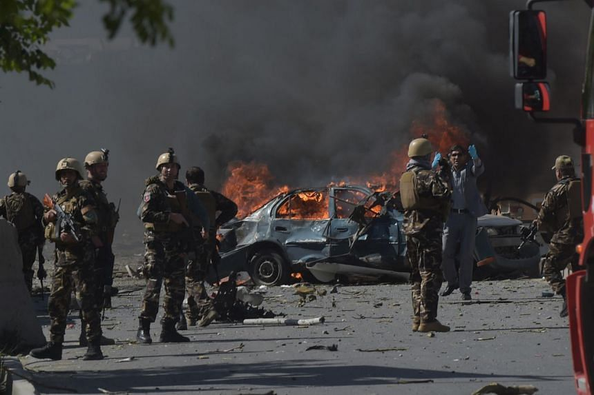 Afghan security forces personnel are seen at the site of the blast.