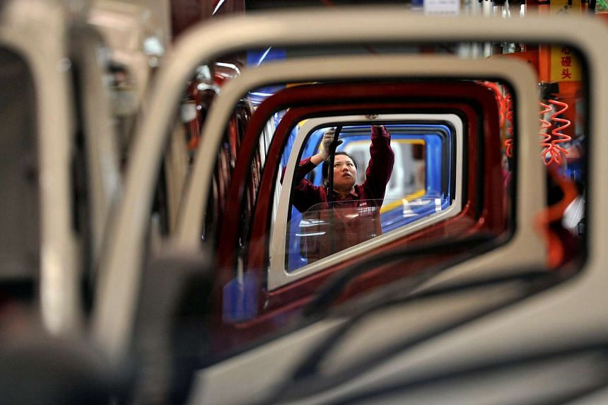 A file picture of a worker installing rubber onto the windows of the doors along a production line at a truck factory of Anhui Jianghuai Automobile Co. Ltd (JAC Motors) in Hefei, Anhui province. PHOTO: REUTERS