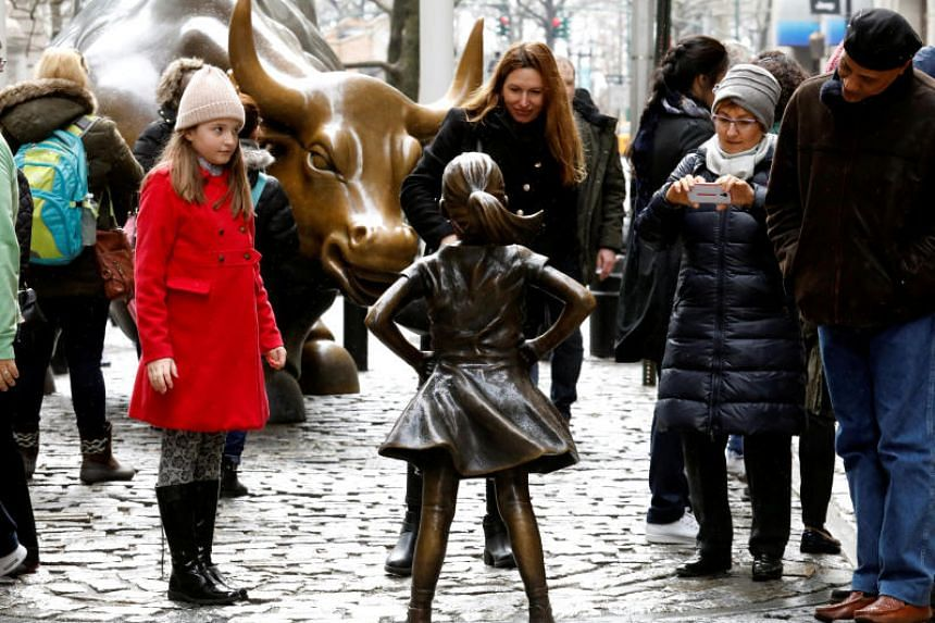 Fearless Girl statues stands across from the iconic Wall Street charging bull statue.