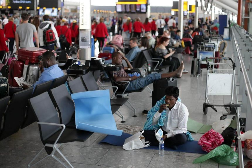 A passenger, directly affected by a global computer crash that disrupted British Airways flights, rests on the floor of Terminal 5 of London's Heathrow Airport on May 29, 2017.