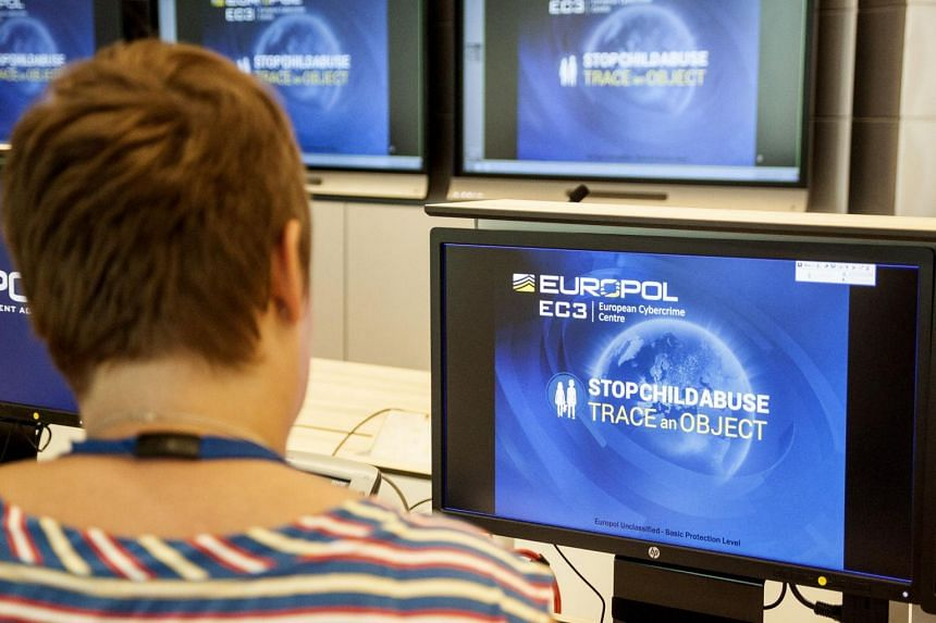 A Europol police agent looks at the onscreen logo of a new website launched by Europol at their headquarters in The Hague.