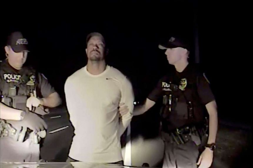 Tiger Woods is seen handcuffed by police officers in this still image from a police dashcam video in Jupiter, Florida on May 29.
