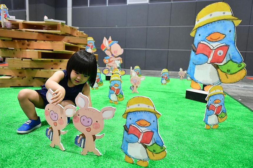 Lee Simin, two, playing with standees of characters created by local illustrator Ah Guo at the Singapore Book Fair at Suntec Singapore Convention & Exhibition Centre yesterday. The event runs till next Monday.