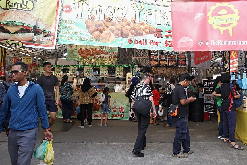 The Geylang Serai Bazaar (above), which features food such as melted cheese (left), was the site of a raid by the authorities on Tuesday as illegal workers were suspected to be working there.