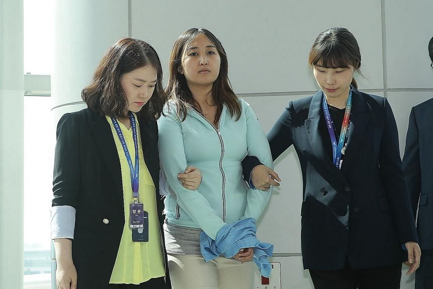 Investigators from the South Korean prosecutors' office escort Chung Yoo Ra after her arrival at Incheon International Airport yesterday from Amsterdam.
