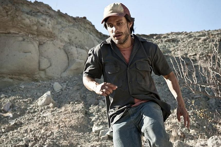 Mexican actor Gael Garcia Bernal (right) plays an illegal migrant being chased across dry sand and rocks by a racist with a hunting rifle.