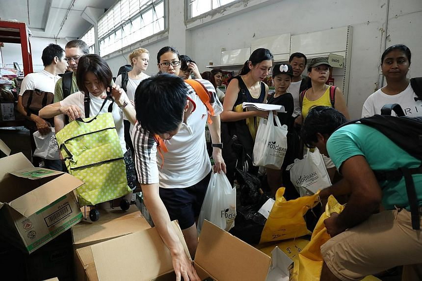 "Dentsu Aegis Network staff cleaning a children's home (top) and packing food bundles at Food Bank (above) that were delivered to Thye Hua Kwan Family Services Centres, as part of the company's ""One Day for Change"" initiative on May 19."