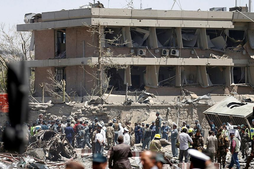 Above: Afghan officials inspecting the damage outside the German Embassy after the blast in Kabul yesterday. From far left: Buildings and vehicles were destroyed, and most of the casualties were Afghans.