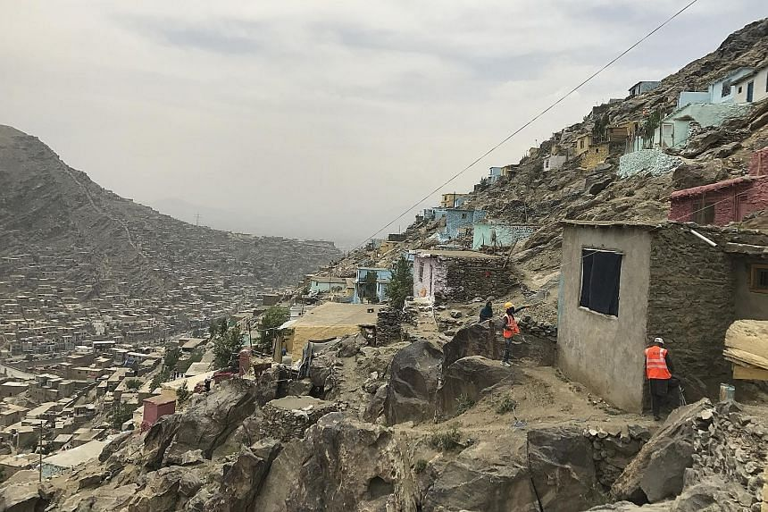 Painters adding colour to the front of a hillside home in Kabul. While many residents have been supportive of the effort, some activists feel it is better to focus on paving paths to the homes high up the mountains or providing water to houses whose