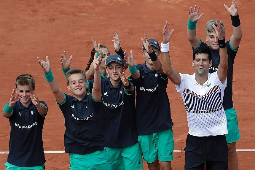 Novak Djokovic celebrating with the ball boys after his second-round French Open win. He will next play Diego Schwartzman.