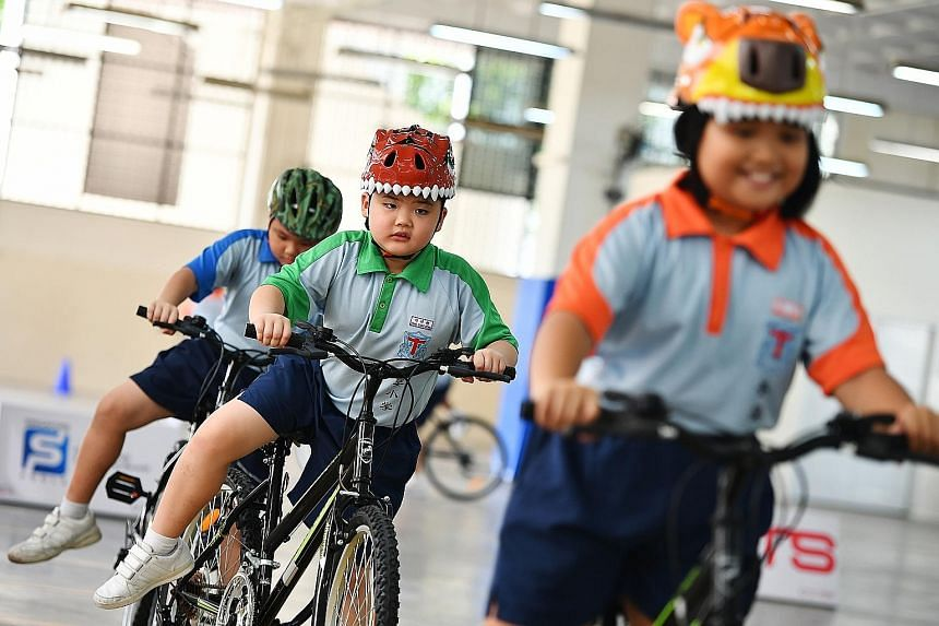 Primary 2 pupil Tang Xiang Rong (centre), eight, is one of 21 pupils from Holy Innocents' Primary School taking part in the two-day Singapore Cycle Safe programme, launched yesterday. It also aims to combat childhood obesity. To make the learning fun