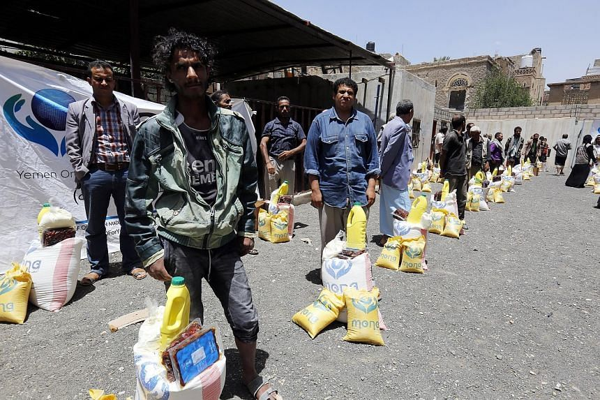 Yemenis collecting food rations in Sana'a, Yemen, last Thursday. UN officials are working to avert a Saudi-led attack on a key port, where some 80 per cent of Yemen's food imports arrive.