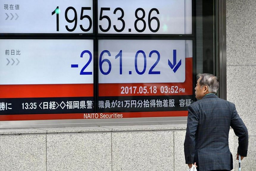 A pedestrian looks at a display showing closing figures of Tokyo's benchmark Nikkei Stock Average in Tokyo.