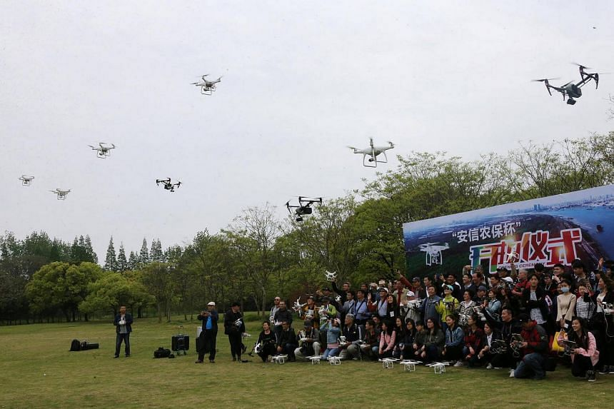 People fly their drones during the launch ceremony of an aerial photography contest in Shanghai.