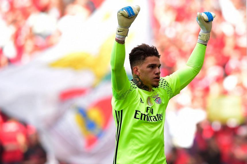 Benfica's Brazilian goalkeeper Ederson Moraes celebrates their second goal scored by teammate Mexican forward Raul Jimenez during the Portuguese league football against Vitoria Guimaraes SC at the Luz stadium in Lisbon on May 13, 2017.