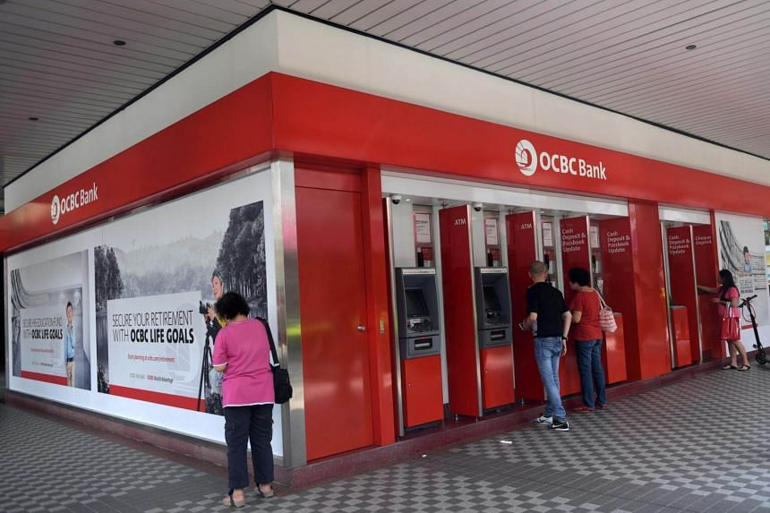 Customers using the automated teller machines at OCBC bank in Tampines.