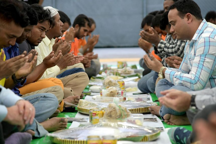 Migrant workers prays before breaking fast at PLQ project site office with Fatimah Lateef and Lendlease executives.