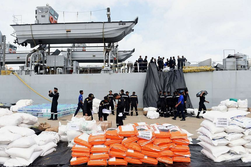 Indian Navy troops offload emergency supplies from the Indian ship Shardul at Colombo harbour in Colombo on May 28, 2017.