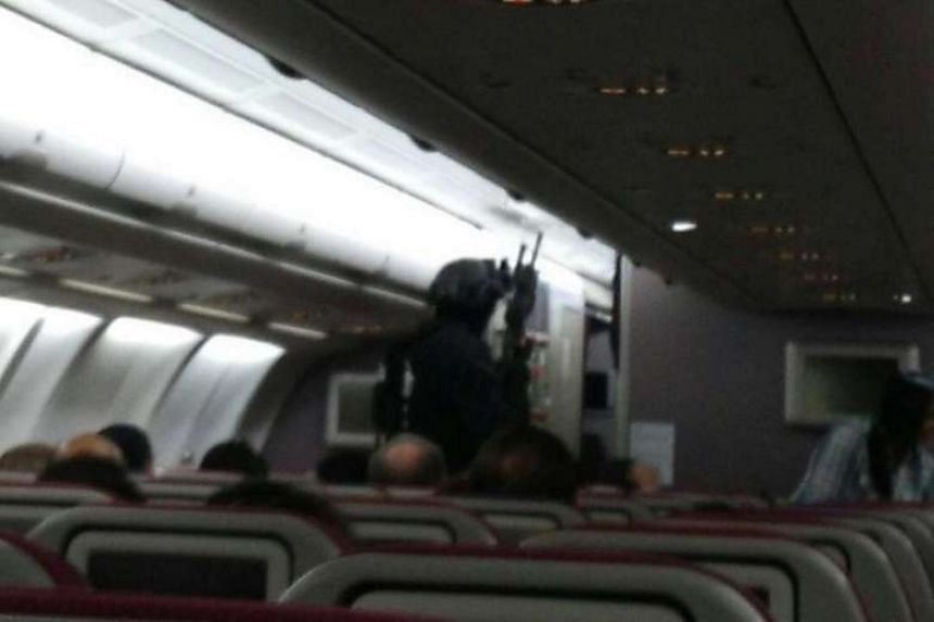 Armed police on board flight MH128, which was diverted back to Melbourne Airport.