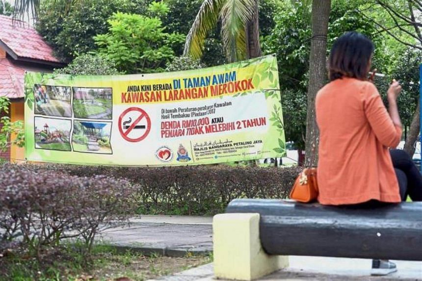 A model pretending to light a cigarette in front of a banner notifying smokers of the ban.