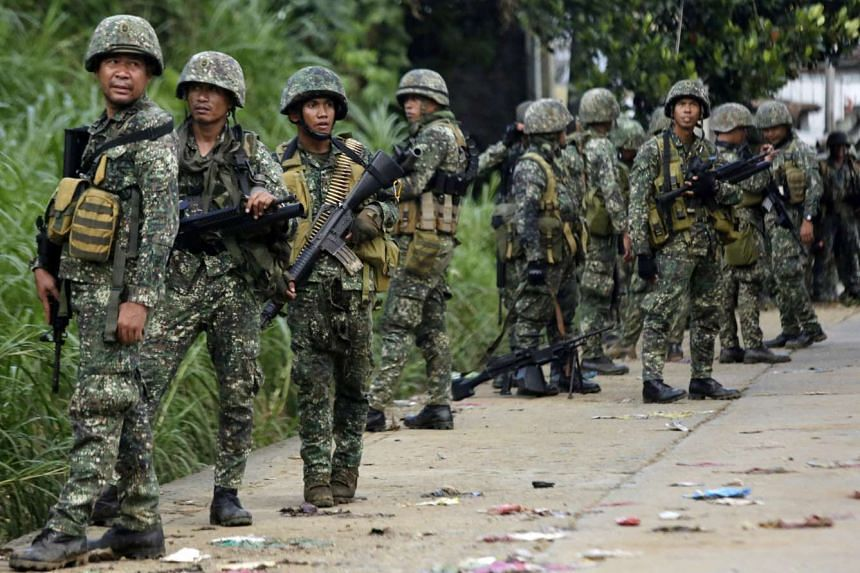 Filipino soldiers advance their position on the fifth day of continued fighting between militants and government forces in Marawi city on May 28, 2017.