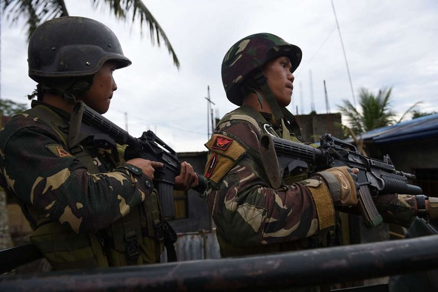 Philippine soldiers stand guard aboard their truck as they escort rescue workers after evacuating trapped residents from their homes on May 31, 2017.