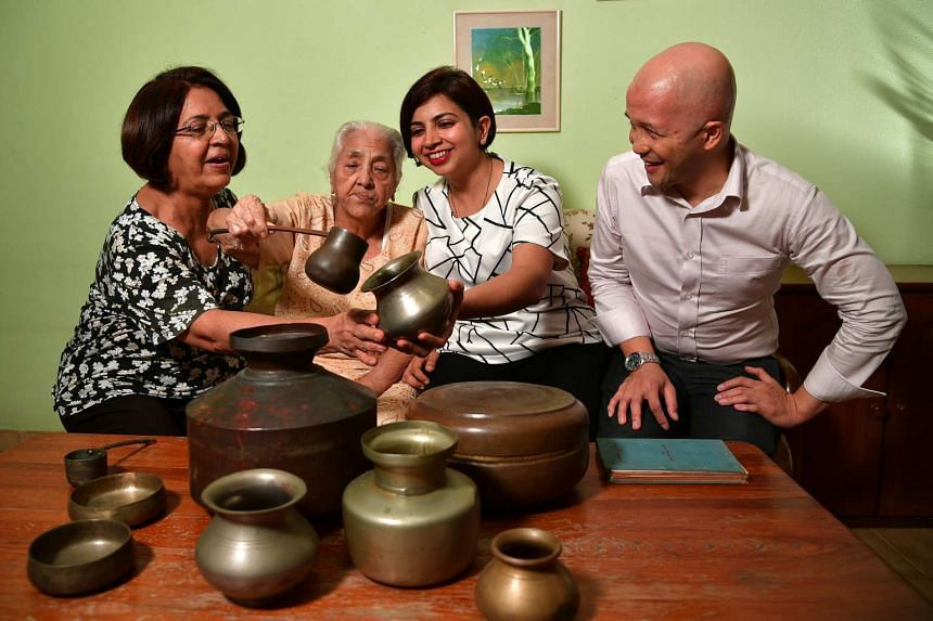 Madam Mohini Kalwani (second from left), with (from left) daughter Shanta Kotwani and grandchildren Babita Kotwani and Laremy Lee, displaying the household utensils she brought to Singapore from Sindh, which she said her mother-in-law told her to do.