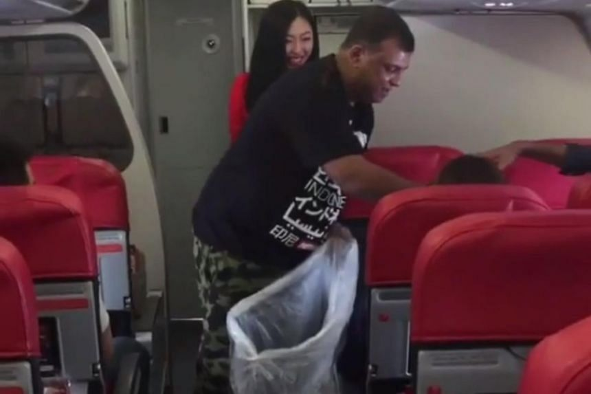 AirAsia chief executive Tony Fernandes paid tribute to his staff by collecting rubbish on board a packed AirAsia flight.
