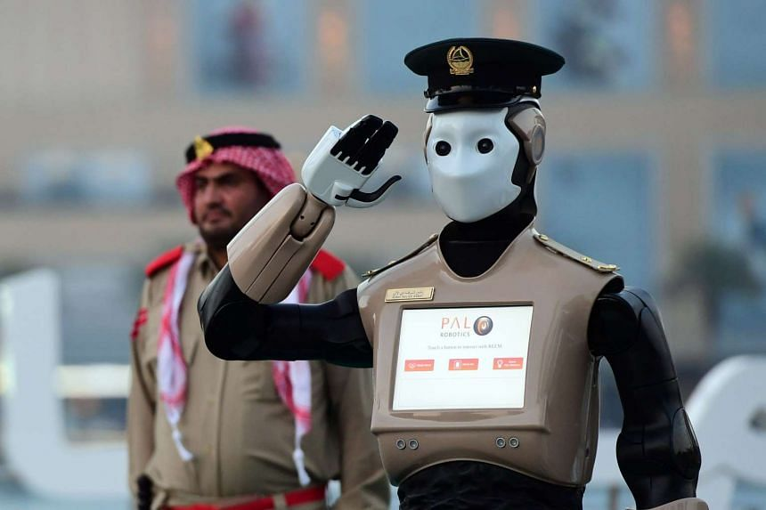 The world's first operational police robot stands at attention they prepare military cannon to fire to mark sunset and the end of the fasting day for Muslims observing Ramadan, in Downtown Dubai on May 31, 2017.