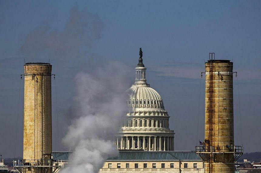 The dome of the US Capitol is seen behind the smokestacks of the Capitol Power Plant.