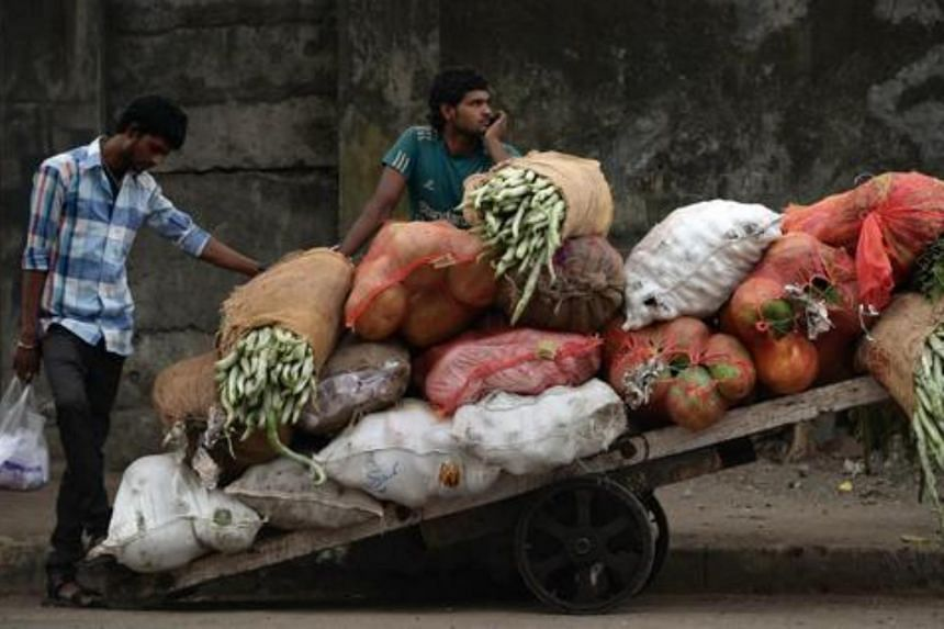 An Indian vendor waits alongside his cart filled with vegetables at the whole sale market in Mumbai.