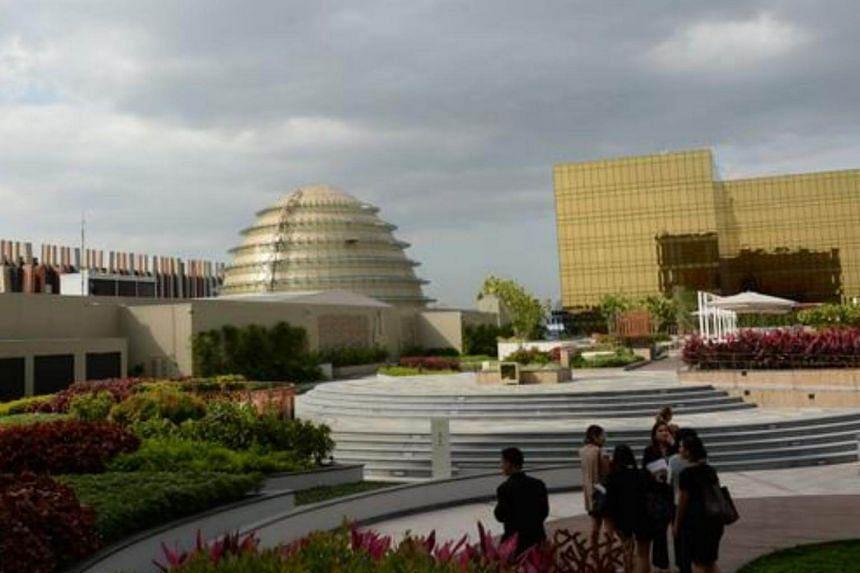 "Visitors walk near the golden dome called the ""Fortune Egg"" of the  City of Dreams mega-casino in Manila."