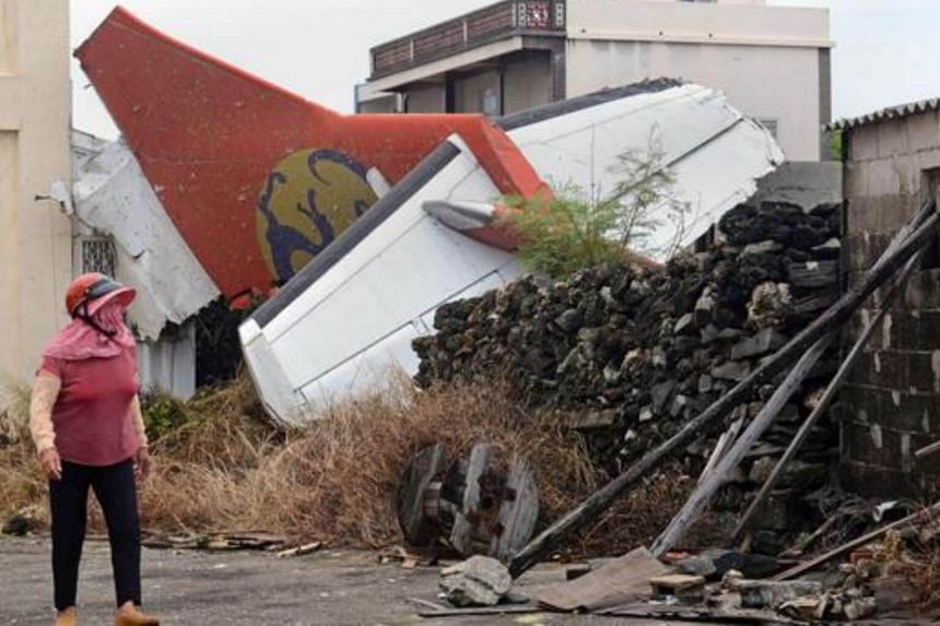 A local resident walking past the tail section of TransAsia Airways flight GE222 as rescue workers and firefighters search through the wreckage the morning after it crashed near the airport at Magong on the Penghu island chain on July 24, 2014.