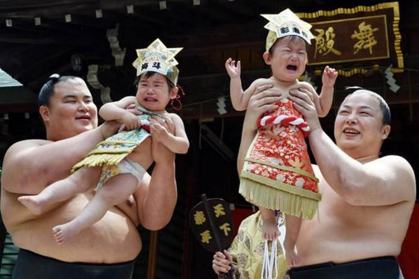 """Sumo wrestlers from Onoe stable hold up crying babies during a """"Baby-cry Sumo"""" event at the Yukigaya Hachiman shrine in Tokyo on April 29, 2015."""