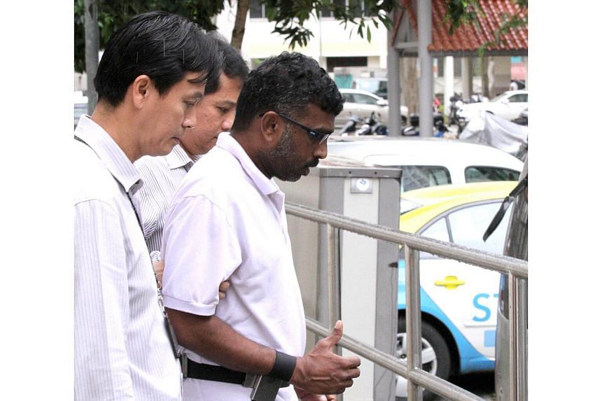 P. Mageswaran who was charged in court on 19 December 2013 with strangling Madam Kanne Lactmy, 62, was escorted to the scene of the crime by the police on Dec 23.