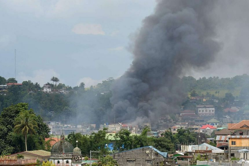 Smoke billows from houses after aerial bombings by Philippine Airforce planes on Islamist militant positions in Marawi, on the southern island of Mindanao on June 2, 2017.