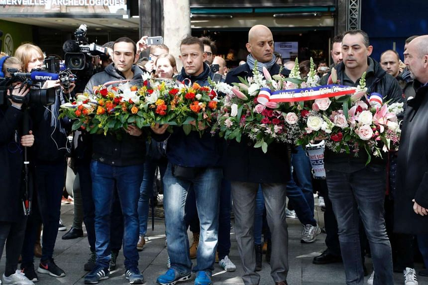 People prepare to lay flowers at the site where a police officer was killed by a terrorist on the Champs Elysees, on April 26, 2017.