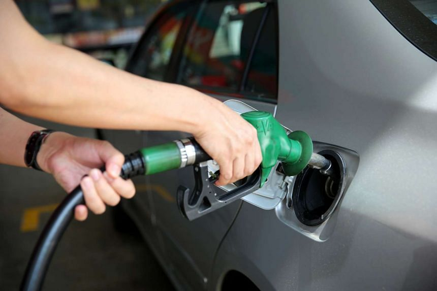A person filling up a car with petrol.