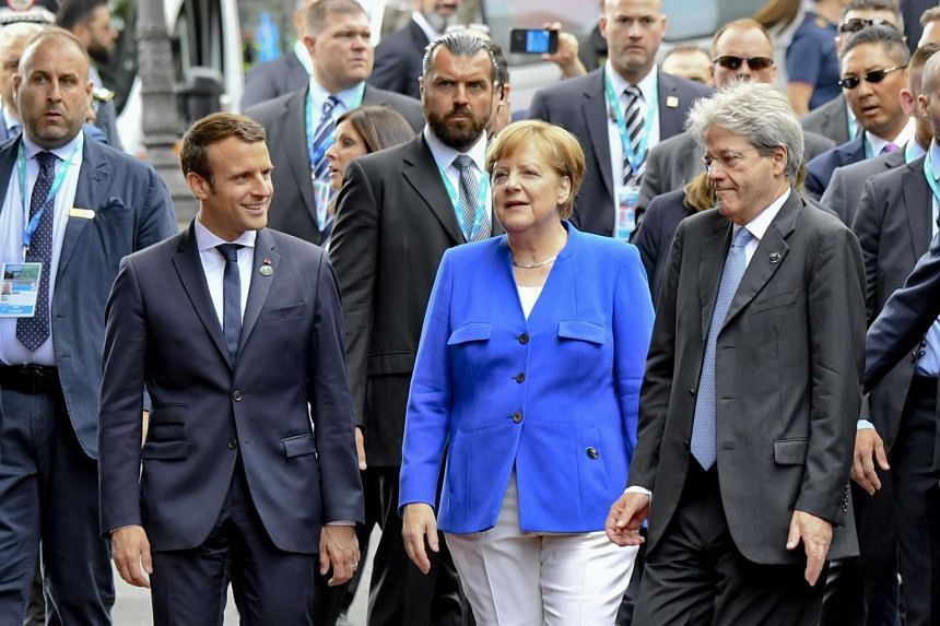 Macron (second left), Merkel (centre) and Gentiloni (right)  are pictured on the first day of the recent Group of Seven summit.