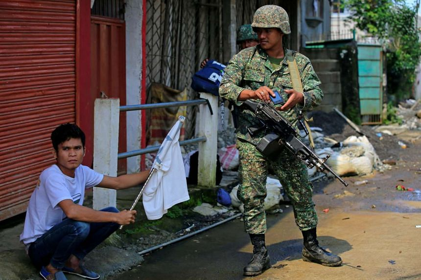 A government soldier looks at a man holding a white flag who fled his home in Marawi City, Philippines on June 1, 2017.